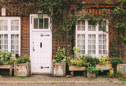 Cottage with white front door and planters outside