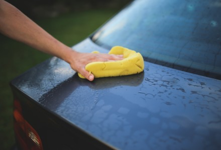 man hand washing black car